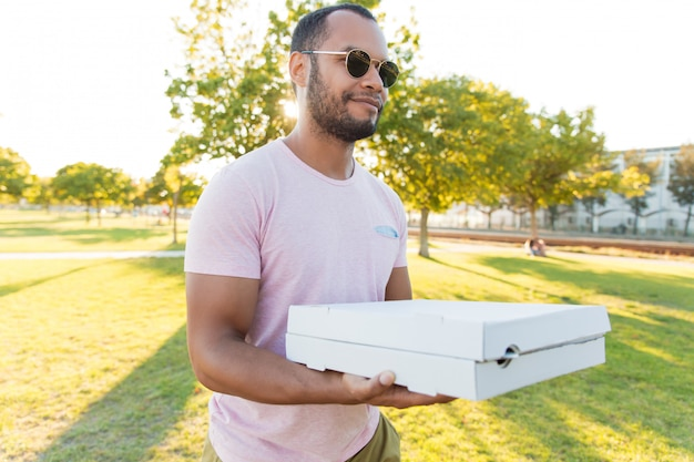 Ragazzo bello positivo amichevole che trasportano pizza