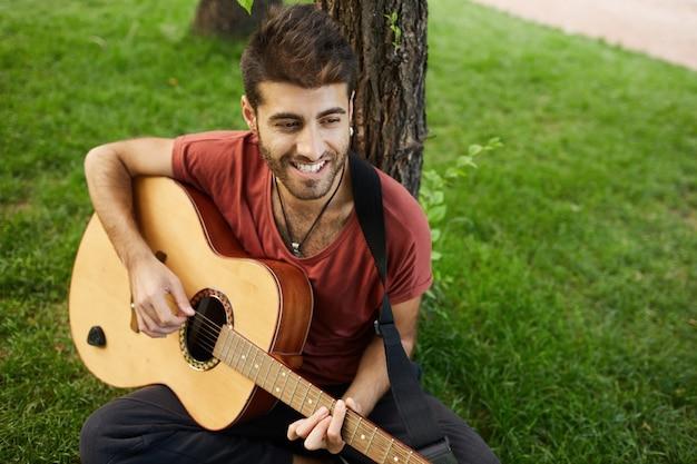 Ragazzo bello spensierato, suonare la chitarra nel parco