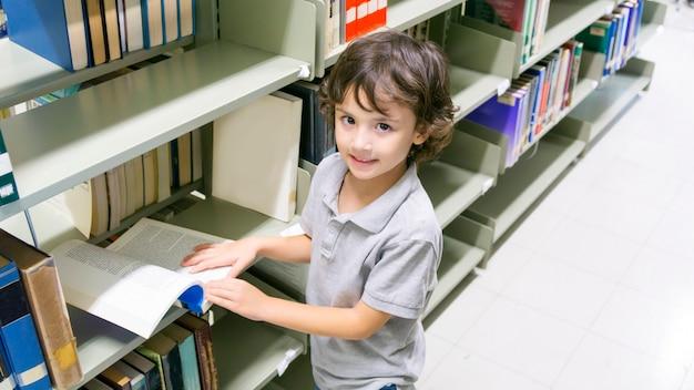 Ragazzo bianco di smiley con il libro e lo scaffale per libri a priorità bassa.