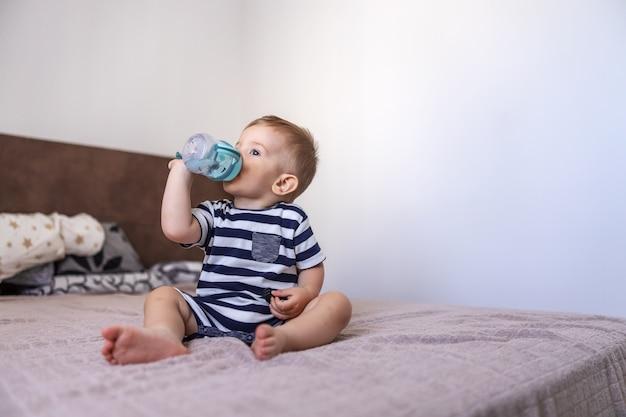 Ragazzo biondo carino seduto sul letto in camera da letto e acqua potabile dalla sua bottiglia.