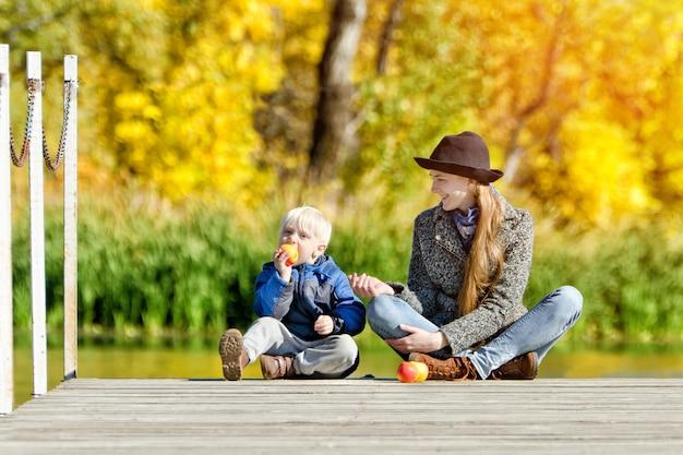 Ragazzo biondo che mangia una mela con sua madre sul bacino. soleggiato, autunno