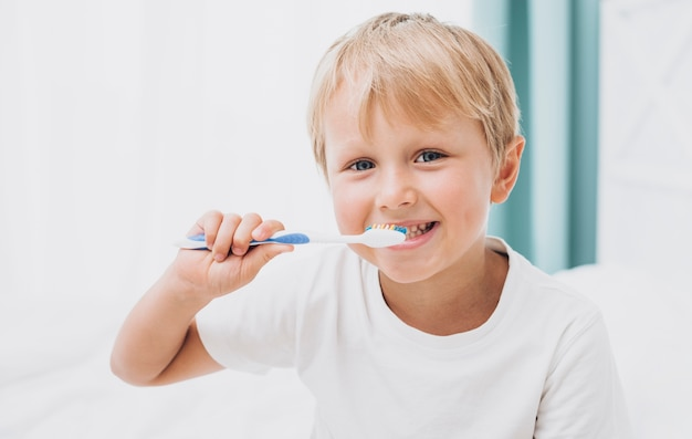 Ragazzo biondo che pulisce i suoi denti