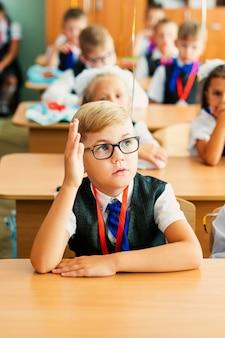 Ragazzo biondo con grandi occhiali neri seduto in aula, studiando, sorridendo. istruzione sulla scuola elementare, primo giorno a scuola