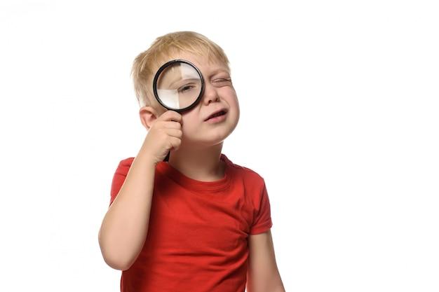 Ragazzo biondo con una lente d'ingrandimento in mano
