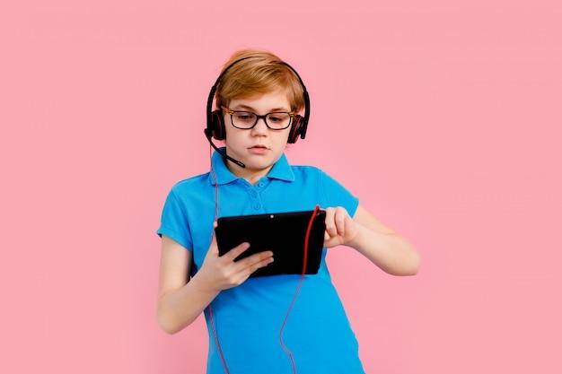 Ragazzo biondo in maglietta che tiene una compressa e che ascolta la musica sulle sue cuffie