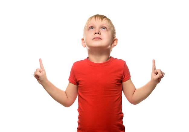 Ragazzo biondo in una maglietta rossa è in piedi e punta con il dito indice verso l'alto