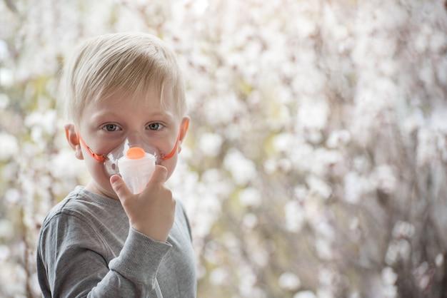 Ragazzo biondo nell'inalatore della maschera respiratoria su un fondo degli alberi di fioritura. trattamento domiciliare. prevenzione