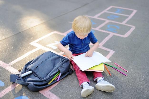 Ragazzo biondo sveglio che fa lavoro che si siede sull'iarda della scuola dopo la scuola con le borse che si situano vicino.