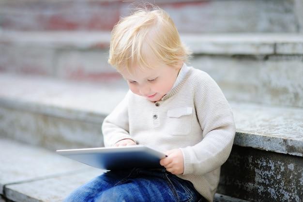 Ragazzo biondo sveglio del bambino che gioca con una compressa digitale all'aperto