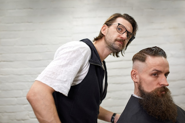 Ragazzo brutale nel moderno barber shop. il parrucchiere fa acconciatura un uomo con la barba lunga. il maestro parrucchiere fa acconciatura con forbici e pettine