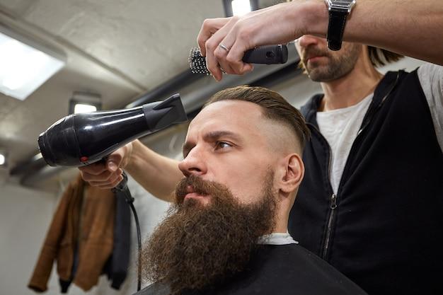 Ragazzo brutale nel moderno barber shop. il parrucchiere fa acconciatura un uomo con la barba lunga. il maestro parrucchiere fa acconciatura con una tosatrice