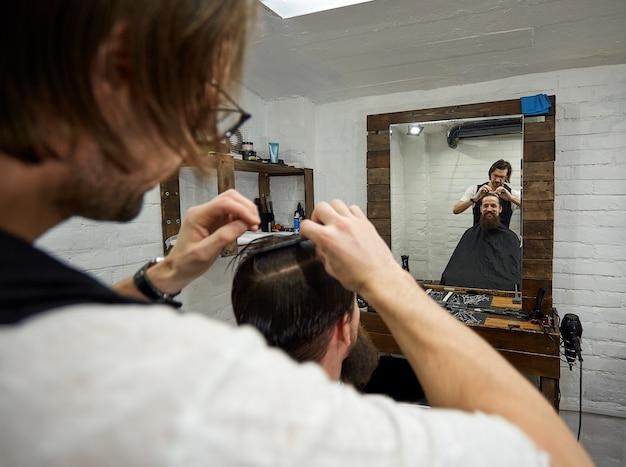 Ragazzo brutale nel moderno barber shop. il parrucchiere rende l'acconciatura un uomo con la barba lunga. il maestro parrucchiere fa acconciatura con forbici e pettine