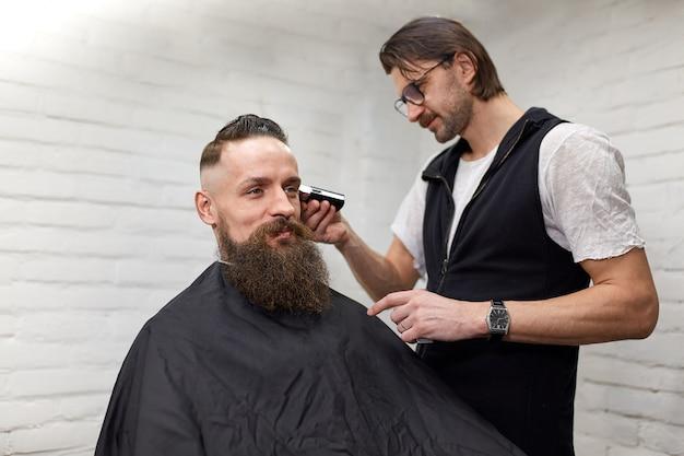 Ragazzo brutale nel moderno barber shop. il parrucchiere rende l'acconciatura un uomo con la barba lunga. il maestro parrucchiere fa acconciatura con una tosatrice
