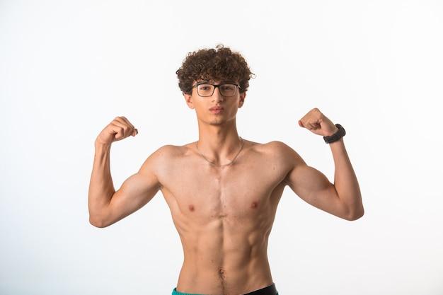 Ragazzo capelli ricci in occhiali optique che mostra i suoi muscoli del corpo in posizione nuda.