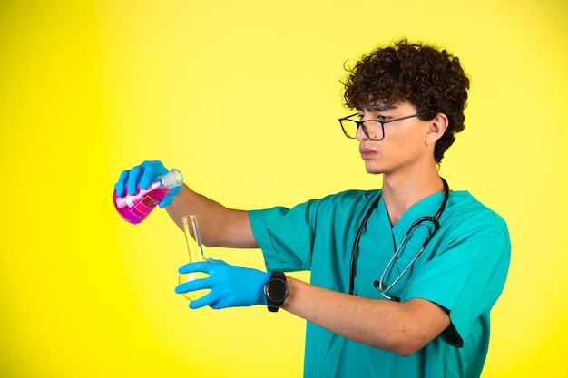 Ragazzo capelli ricci in uniforme medica e maschere per le mani che fanno reazione chimica con boccette.
