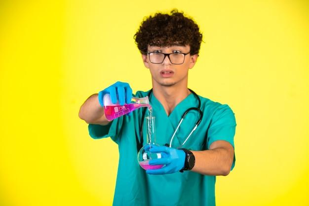 Ragazzo capelli ricci in uniforme medica e maschere per le mani che fanno reazione chimica.