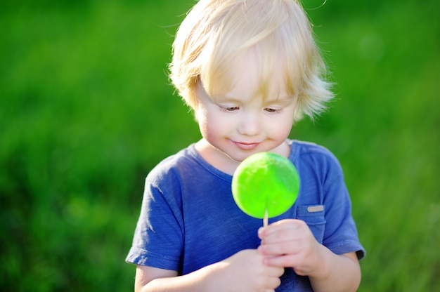 Ragazzo carino bambino con grande lecca-lecca verde. bambino che mangia dolce candy bar. dolci per bambini piccoli. divertimento estivo all'aperto