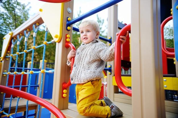 Ragazzo carino bambino divertendosi nel parco giochi. gioco attivo all'aria aperta per i più piccoli