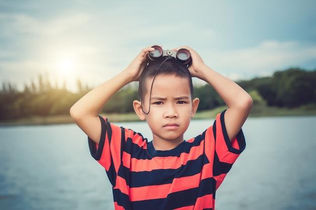 Ragazzo carino bambino in piedi sulla riva del fiume e con spyglass.
