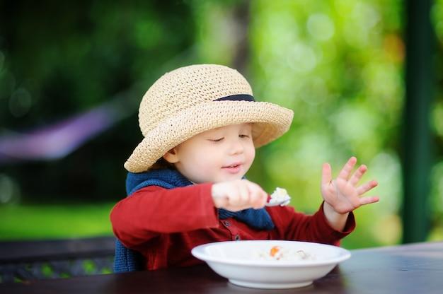 Ragazzo carino bambino mangiando cereali di riso all'aperto. cibo sano per i più piccoli
