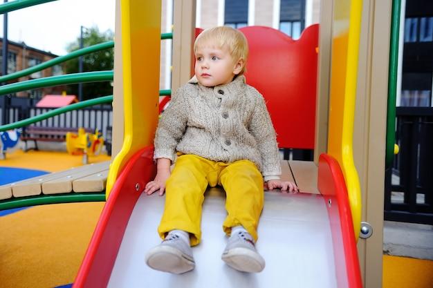 Ragazzo carino bambino sul parco giochi. gioco attivo all'aria aperta per i più piccoli