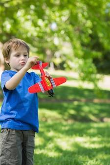 Ragazzo carino con aeroplanino giocattolo al parco