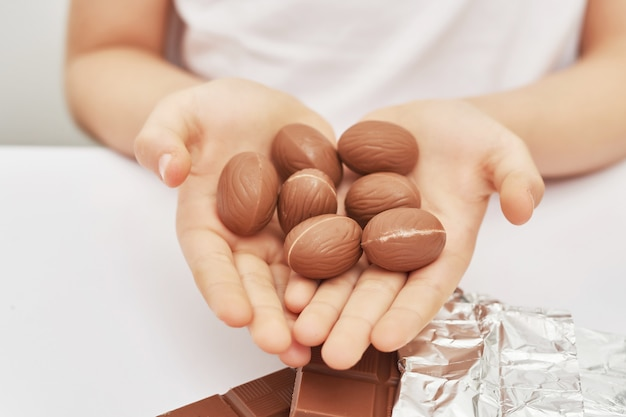 Ragazzo carino con coniglietti al cioccolato e uova per pasqua. uova di cioccolato, conigli e piastrelle. dolci al cioccolato per bambini