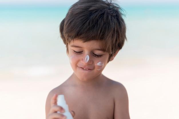 Ragazzo carino con crema solare in spiaggia