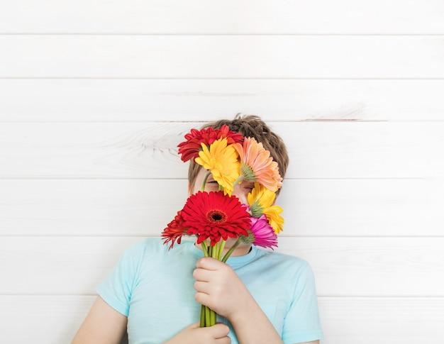 Ragazzo carino con fiori di gerbera bouquet. festa della mamma, primavera, concetto di pasqua.