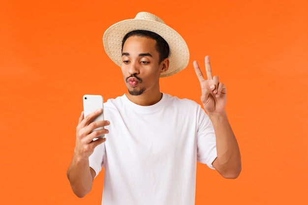 Ragazzo carino e felice afro-americano in maglietta bianca, cappello estivo, mostrando il segno di pace, prendendo selfie con filtro piega labbra bacio, guardando smartphone, pubblica foto dalle vacanze, arancione