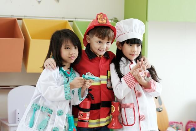 Ragazzo carino e ragazze che giocano come vigile del fuoco, medico e cuoco occupazione nella classe di scuola materna