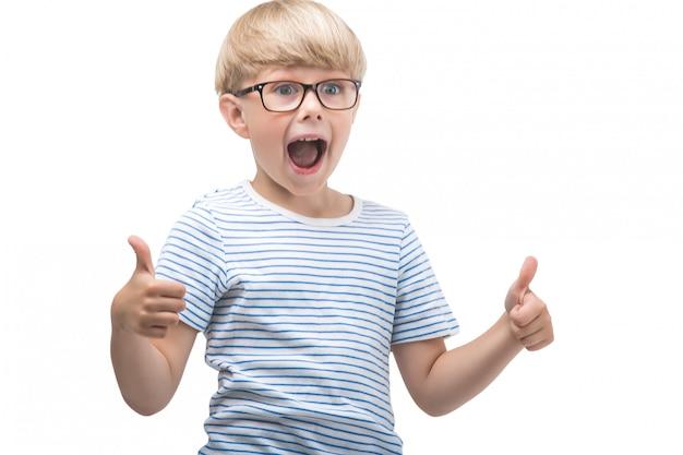 Ragazzo carino emotivo mostrando ok o pollice in su. adorabile bambino su sfondo isolato. lo studio ha sparato di scolaro.