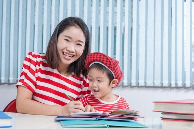 Ragazzo carino facendo i compiti scolastici con la madre, a casa, sta scrivendo su un libro