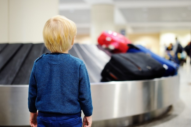 Ragazzo carino piccolo ragazzo stanco all'aeroporto, viaggiando. bambino sconvolto che aspetta con la valigia dei bambini sul carosello del bagaglio.