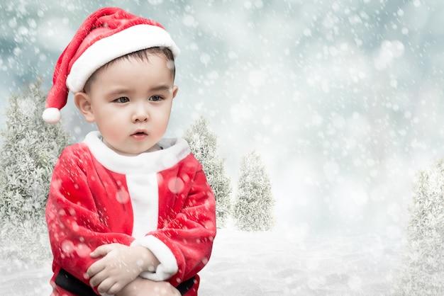 Ragazzo carino santa con la neve che cade