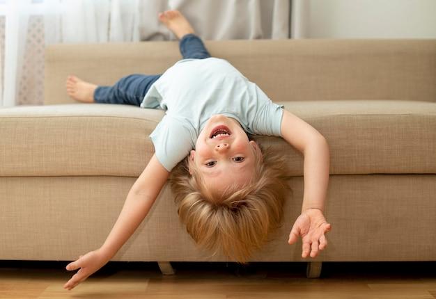 Ragazzo carino sul divano a giocare