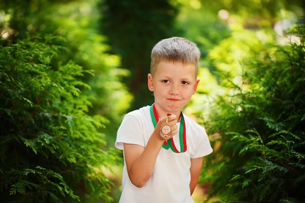 Ragazzo carino, tenendo e mostrando le medaglie annuncio sport day