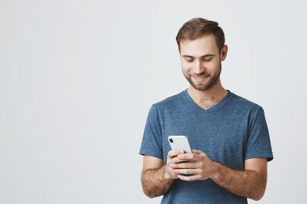 Ragazzo caucasico bello mandare sms, utilizzando il telefono cellulare