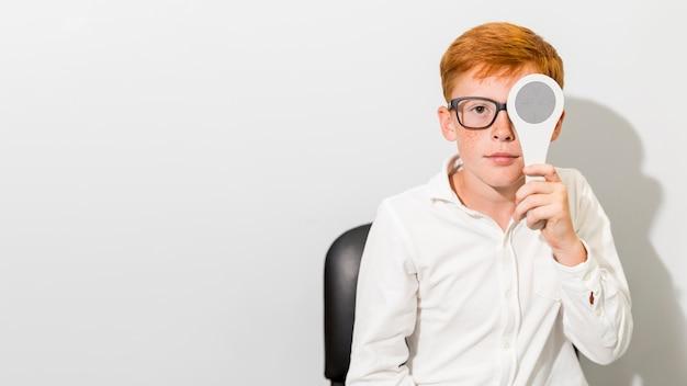 Ragazzo caucasico con gli occhiali che tengono occluder davanti al suo occhio