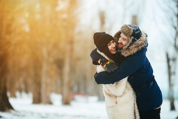 Ragazzo che abbraccia la sua ragazza in un parco innevato