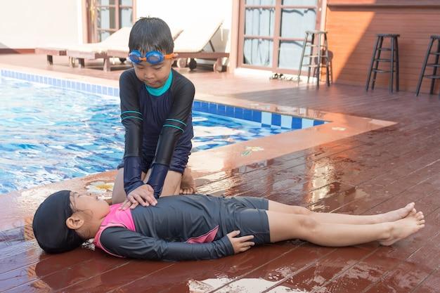 Ragazzo che aiuta annegando ragazza del bambino nella piscina facendo cpr.