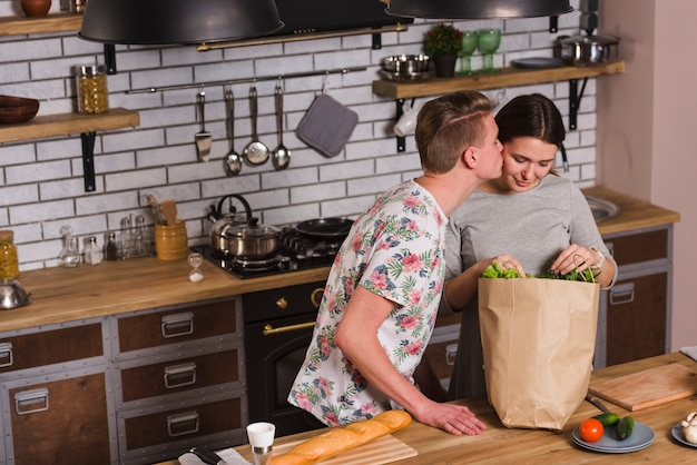 Ragazzo che bacia donna con generi alimentari