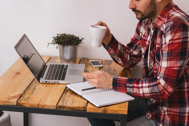 Ragazzo che compra online con un computer portatile e una carta di credito