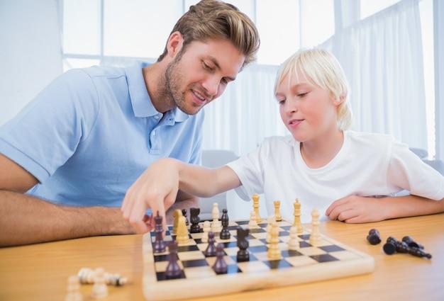 Ragazzo che gioca a scacchi con suo padre