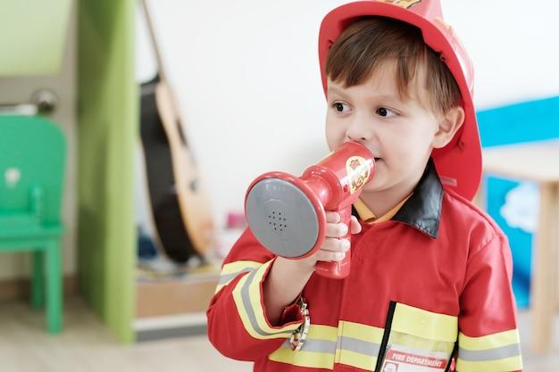 Ragazzo che gioca come occupazione della polizia del vigile del fuoco nella classe dell'asilo, occupazione del bambino, concetto di istruzione