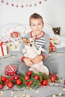 Ragazzo che gioca con il cane jack russell su un letto con decorazioni di capodanno