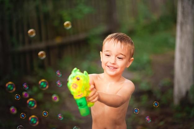 Ragazzo che gioca con il primo piano delle bolle di sapone e lo spazio della copia.