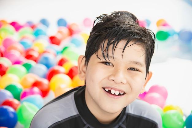 Ragazzo che gioca con la palla variopinta in piccolo giocattolo della piscina