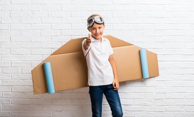 Ragazzo che gioca con le ali dell'aeroplano del cartone sul suo handshaking posteriore dopo il buon affare