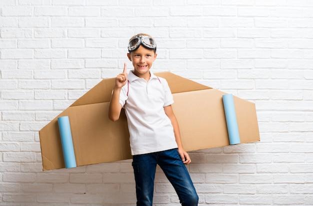 Ragazzo che gioca con le ali dell'aeroplano del cartone sul suo parte posteriore che conta il segno di numero uno